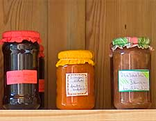 Image of decorated jam jars displayed in a pine cabinet
